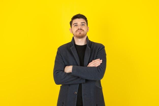 Ritratto di giovane uomo bello incrociò le braccia su un giallo.