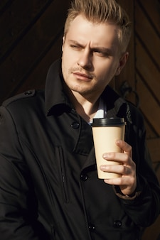 Portrait of young handsome man in dark coat with cup of coffee standing near old gate