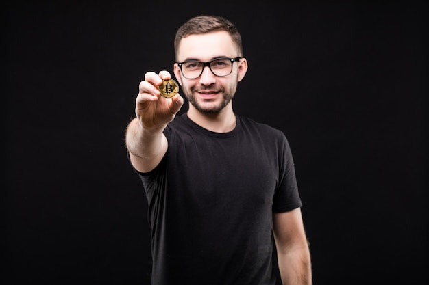 Portrait of young handsome man in glasses in black shirt pointed golden bitcoin on camera isolated on black