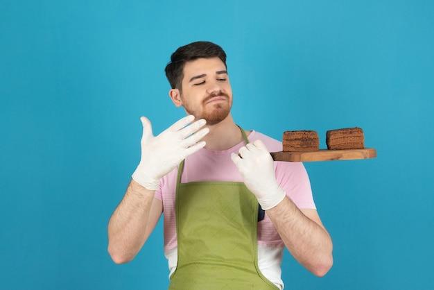 Ritratto di giovane uomo bello che tiene fette di torta fresca fatta in casa.