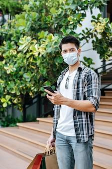 紙袋を保持している保護マスクの肖像画若いハンサムな男