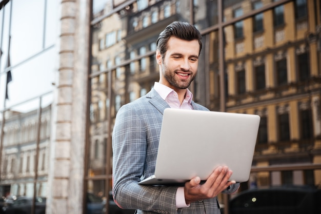 Portrait of a young handsome man in jacket holding laptop