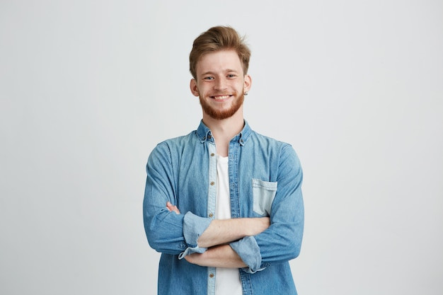 Portrait of young handsome man in jean shirt smiling with crossed arms.