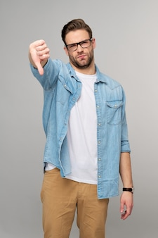 Portrait of young handsome man in jeans shirt showing big thumb down dislike gesture standing over light wall