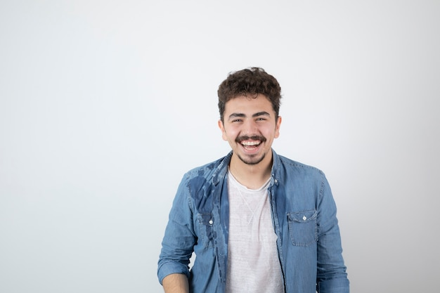 Portrait of a young handsome man model with mustache standing and looking at camera.