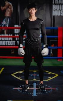 Ritratto giovane uomo bello in abbigliamento sportivo e guantoni da boxe bianchi posa in piedi su tela in palestra per il fitness, lezione di boxe allenamento uomo sano,