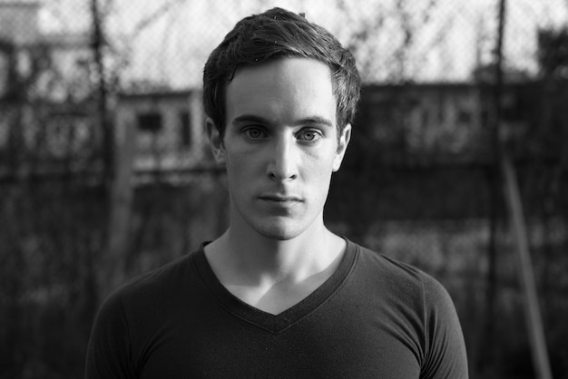 Portrait of young handsome man in the streets outdoors in black and white