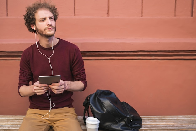 Portrait of young handsome man using his digital tablet outdoors in the street. technology and urban concept.