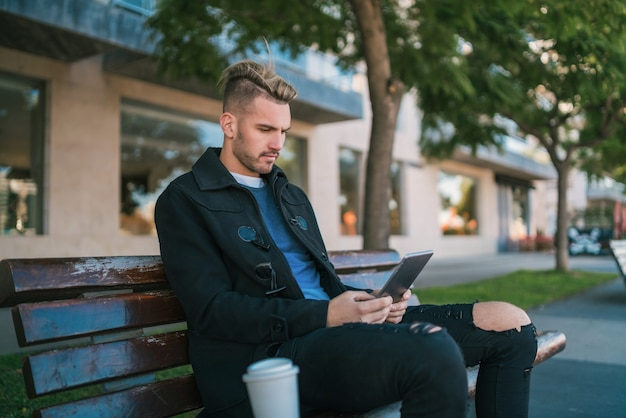 Ritratto di giovane uomo bello utilizzando la sua tavoletta digitale all'aperto mentre è seduto su una panchina.