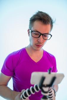 Portrait of young handsome man vlogging on hue of blue light