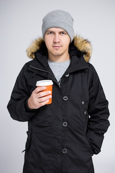 Portrait of young handsome man in warm winter jacket drinking coffee or tea over gray background