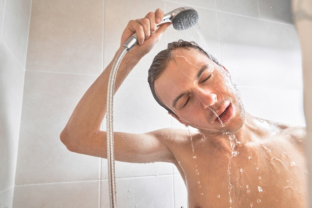 Portrait of young handsome man washes himself with shower gel, lathers head with shampoo in the bathroom at home close-up