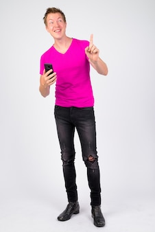 Portrait of young handsome man wearing purple shirt against white wall