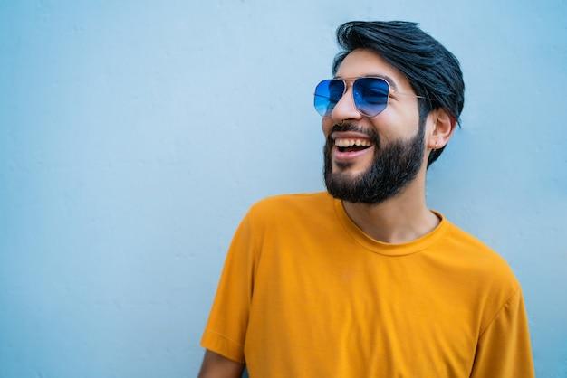 Ritratto di giovane uomo bello che indossa abiti estivi e occhiali da sole contro lo spazio blu.