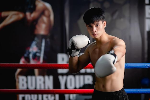 Ritratto giovane uomo bello in guanti da boxe bianchi in piedi posa su tela in palestra, alza le braccia mostra muscoli perfetti, lezione di boxe allenamento uomo sano,,