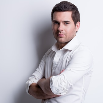 Ritratto di giovane uomo bello in camicia bianca pone sul muro con ombre di contrasto.