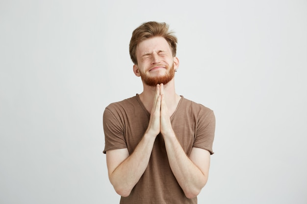 Portrait of young handsome man with beard praying hoping.