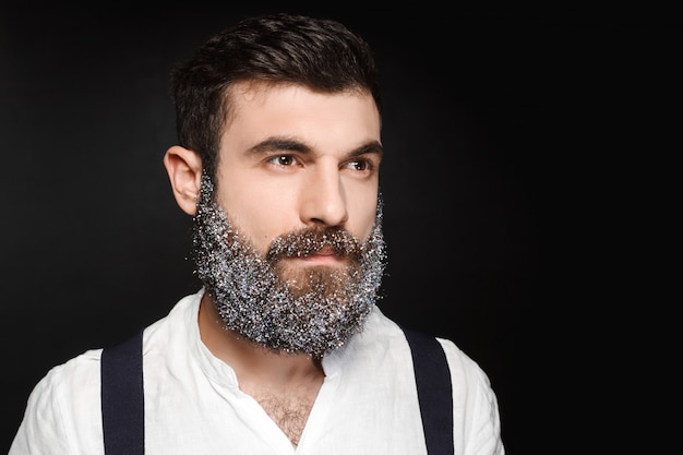 Portrait of young handsome man with beard in snow over black background.