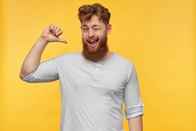 Ritratto di giovane uomo bello con un grosso tallone si sente felice, sorride ampiamente e punta il pollice su se stesso sul giallo.