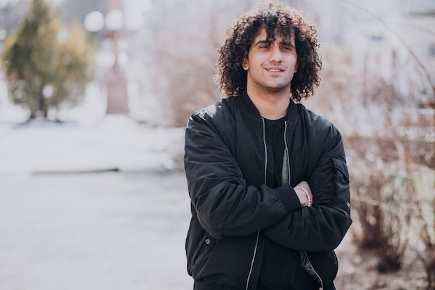 Portrait of young handsome man with curly hair