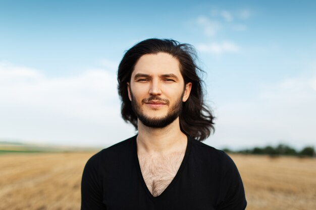 Portrait of young handsome man with long dark hair on background of blue sky.