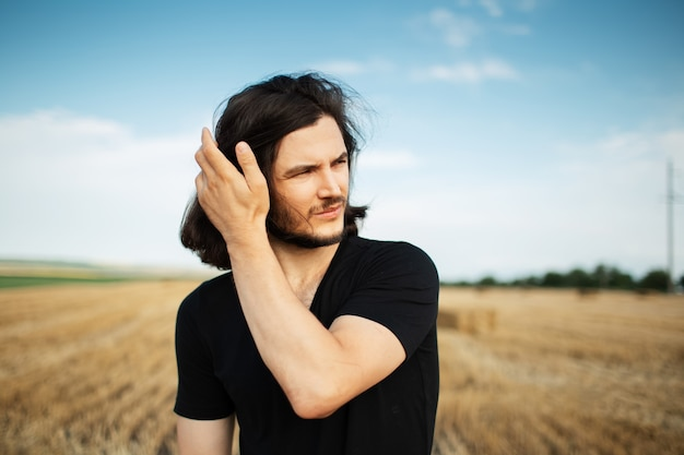 Portrait of young handsome man with long dark hair in wheat field.