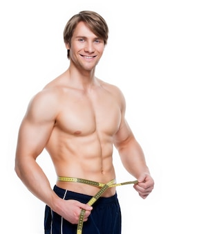 Portrait of a young handsome man with muscular torso uses measuring tape on a white wall.