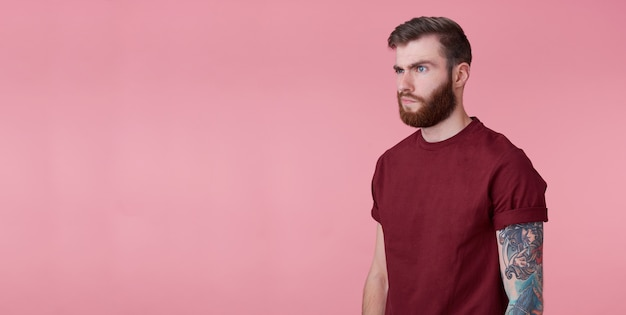 Portrait of young handsome misunderstanding red bearded man in red t-shirt, stands over pink background, looks to copy space on the left side, stands over pink background.