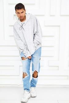 Il ritratto di giovane uomo di modello bello si è vestito in vestiti casuali grigi di maglia con cappuccio che posano vicino alla parete bianca strutturata