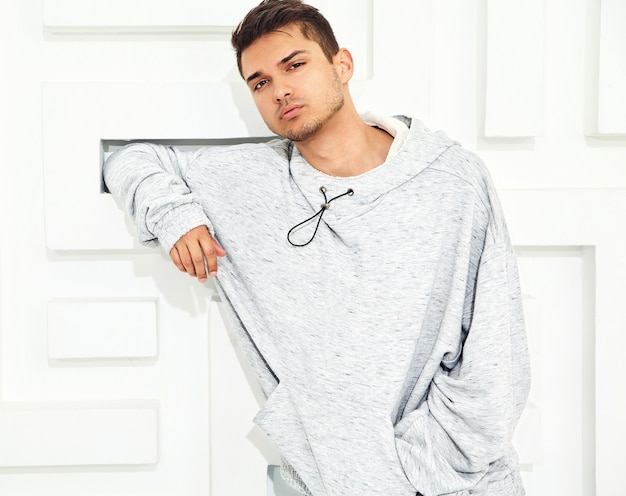 Portrait of young handsome model man dressed in gray casual hoodie clothes posing near textured white wall
