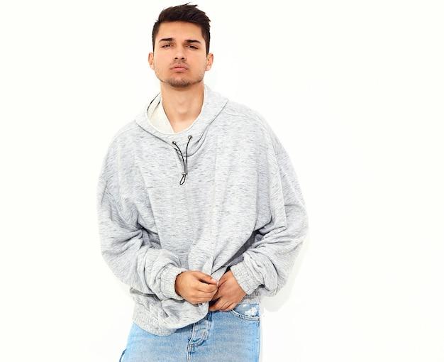 Il ritratto di giovane uomo di modello bello si è vestito in vestiti di maglia con cappuccio casuali grigi che posano sulla parete bianca. isolato