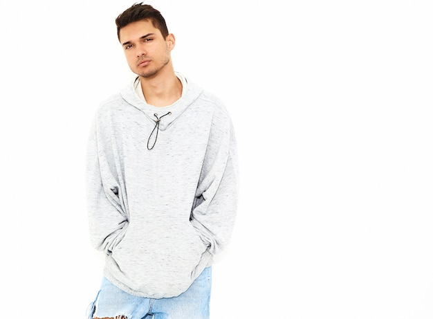 Portrait of young handsome model man dressed in gray casual hoodie clothes posing on white wall. isolated