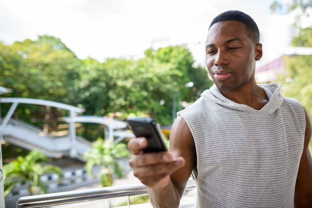 Portrait of young handsome muscular african man ready for gym against view of the city streets