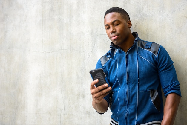 Portrait of young handsome muscular african man wearing blue jacket against concrete wall outdoors