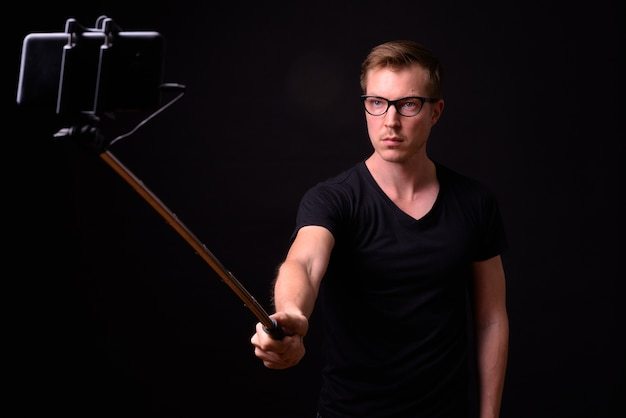 Portrait of young handsome nerd man taking selfie with phone on selfie stick