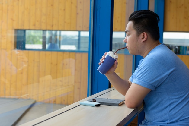 Portrait of young handsome overweight filipino man relaxing at the coffee shop