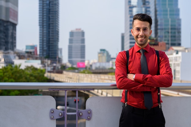 Portrait of young handsome persian businessman exploring the city of bangkok, thailand