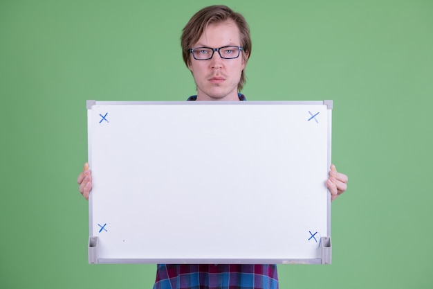 Portrait of young handsome scandinavian hipster man with eyeglasses against chroma key or green wall