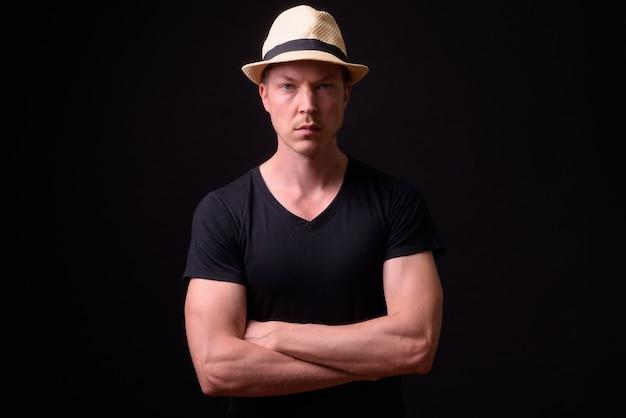 Portrait of young handsome scandinavian man on black