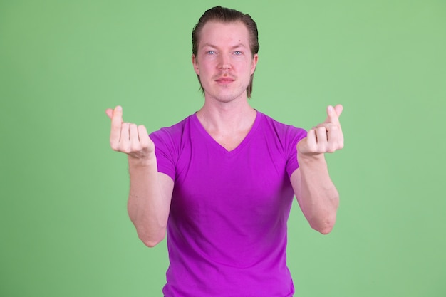 Portrait of young handsome scandinavian man wearing purple shirt against chroma key or green wall