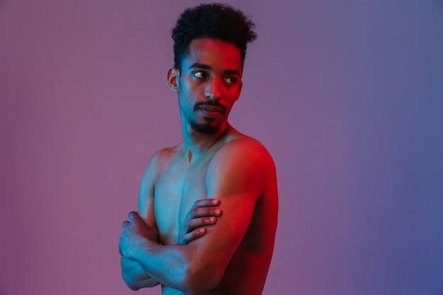 Portrait of young handsome shirtless african american man posingwith his arms crossed isolated over violet wall