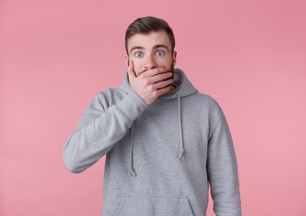 Portrait of young handsome shocked red bearded man in gray hoodie, looks surprised and covers mouth with palm, stands over pink background with wide open eyes.