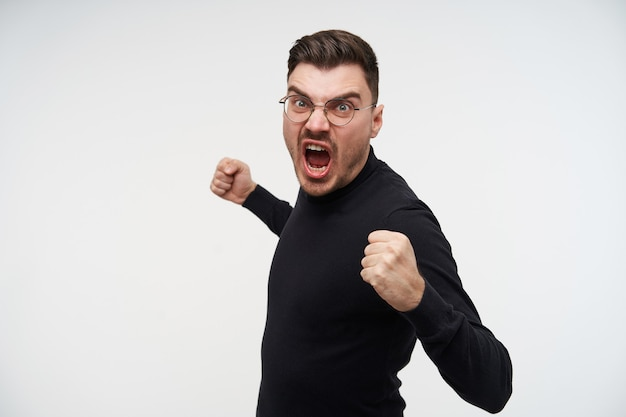 Portrait of young handsome short haired bearded guy in glasses raising his fists and screaming crossly with wide mouth opened, isolated on white