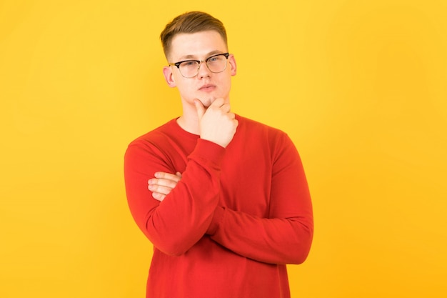 Portrait of young handsome smiling guy in red sweater holding his hand near chin thinking on yellow background