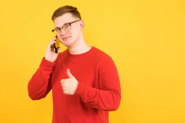 Portrait of young handsome smiling guy in red sweater talking on phone with thumb up