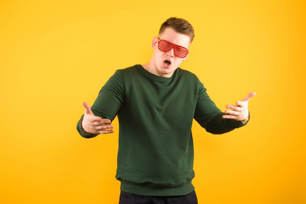 Portrait of young handsome smiling guy with sunglasses showing gesture with open arms