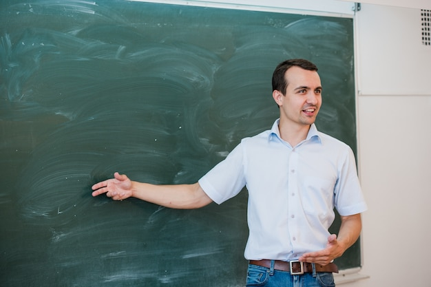 Portrait of young handsome student or teacher in a class pointing at blank chalkboard, talking and smiling