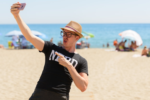 Portrait of young handsome tourist man as nerd at the beach in spain