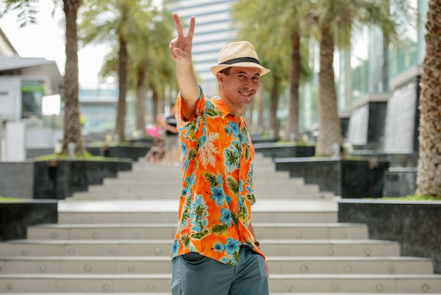 Portrait of young handsome tourist man outside shopping mall in the city