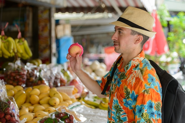 Portrait of young handsome tourist man at the street market outdoors